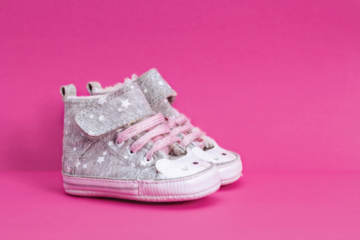 Baby's bootees. Shoes for newborn girl. On pink background