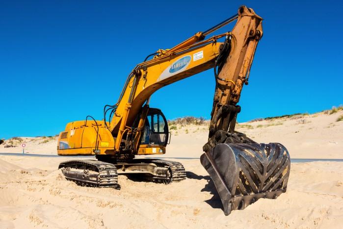 Yellow excavator in the desert